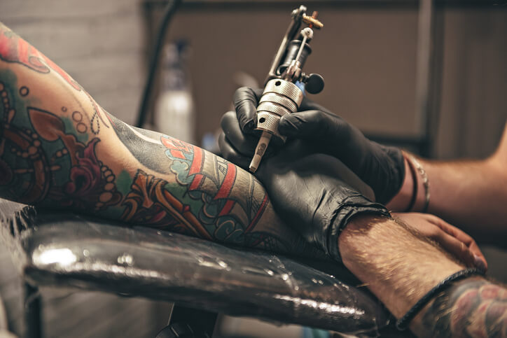 A man getting a forearm tattoo in a tattoo parlor.