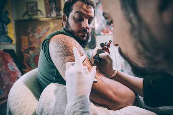 man experiencing pain while getting tattoo